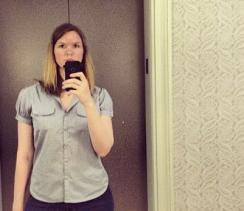 Jessica is in the left side of the image. You can see her from the waist up to her forehead. She is holding an iPhone at neck level, snapping this self portrait. Behind her is an elevator and the cream-colored wallpaper.