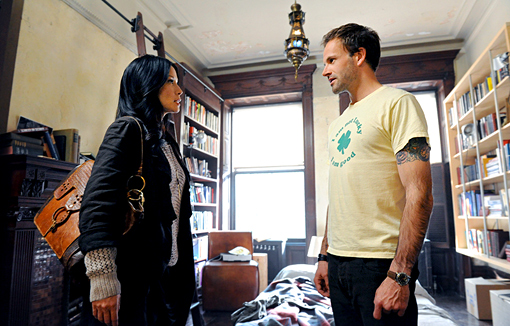 Lucy Liu is on the left in profile. She is wearing a jacket and holding a purse. She's looking at Miller, who is on the right, also in profile. He is wearing a short-sleeved yellow shirt. They appear to be mid-conversation. They are in his apartment, which is messy and has bookshelves full of books.