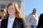 Abigail Fisher, a white woman with red hair dressed in a suit, walks down steps of the US Supreme Court after arguments had been heard in her suit against the University of Texas.