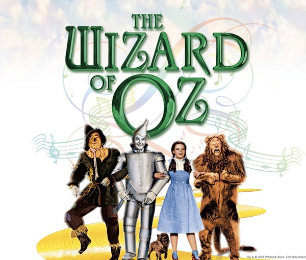 A picture from the Wizard of Oz: the four main characters all in a row looking forward, the yellow brick road behind them.