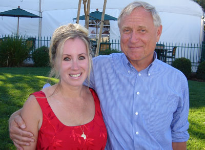 An older white man stands on the right, his arm around a middle-aged white woman. They are both smiling at the camera. He has on a buttoned up blue collar shirt, she is wearing a red dress, her hair swept up.