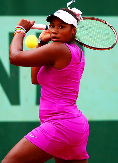 Townsend, a young black lady, is wearing a hot pink tennis outfit, white visor, and is hitting the ball with her racquet.