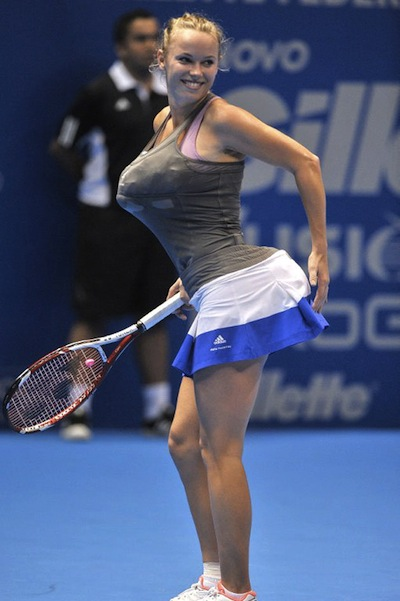Carolina Wozniacki in profile, with her top and skirt stuffed with towels.