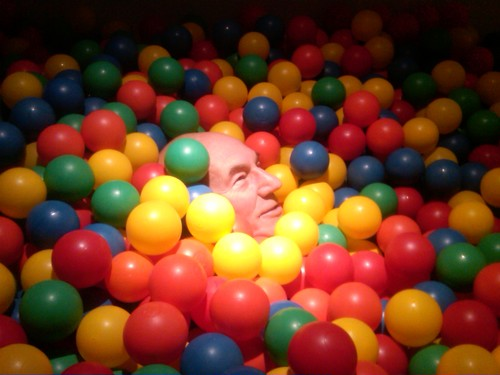 Patrick Stewart in a pile of plastic balls with only his head popping out.