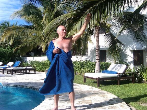 Patrick Stewart, standing next to a pool, wrapped in a big blue towel, saluting like he is Julius Caesar.