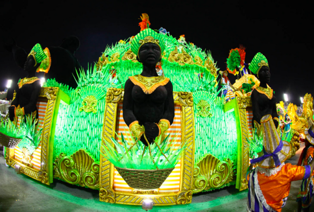 The float is green and on the part facing us is a very dark skinned person carrying a basket.