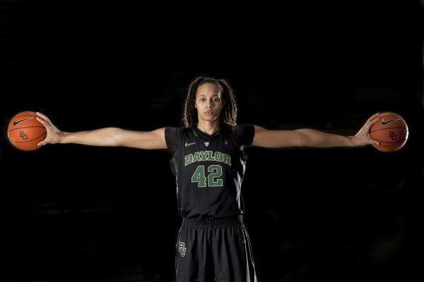 "Brittney Griner's wingspan is 7'4"". She is standing against a black backdrop and is in her black Baylor uniform. Her arms are stretched out to the sides and in each hand is a basketball."