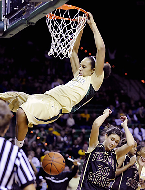 Britney Griner is hanging onto the rim after dunking the ball over a Texas State player.