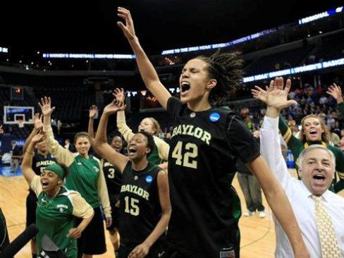Griner, in her black Baylor jersey, is running onto the court in front of her teammates and coaches. They all have their hands in the air in celebration. Griner's eyes are closed and her mouth is open.