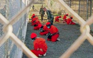 Detainees in Guantanamo Bay, all in orange jump suits, gas masks, and organ beanie hats. They are on their knees, on gravel, behind a chained-link fence. One has turned his head to look toward the camera. There are two white US male soldiers in the pen with the prisoners. The prisoners' hands are handcuffed.