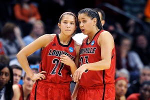 Jude, on the left, and Jodi, on the right, are in their red Louisville uniforms. Shoni is saying something to Jude as they both look forward. Jude is leaning over to listen carefull to Shoni.