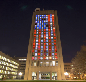 Green Building at MIT last night, displaying a U.S. Flag. The tall, rectangular building has its windows lit up different colors to represent the US flag. The stars are in the upper left and flag is facing down towards the ground. The building faces Boston.