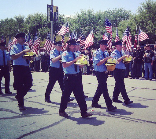 Fire fighters from West Texas are in two lines, walking down a road lined with spectators and American flags. The carry the helmets of those who have fallen in their hands, on person per helmet. They are dressed in blue, formal attire uniforms complete with black caps.