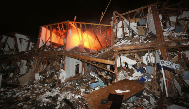 A fire burns in a destroyed apartment complex, near a fertilizer plant that exploded in West, Texas, on April 18, 2013