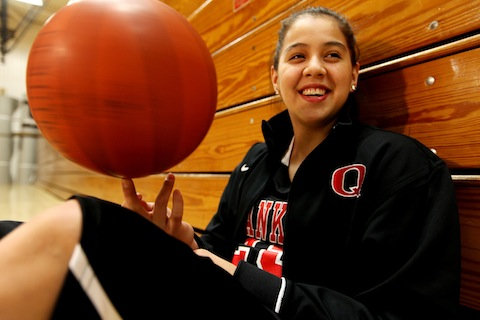 Shoni, back in high school, twirling a basketball like it isn't anything. She is sitting up against closed wooden bleachers. She's smiling.